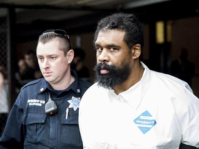 Agentes escoltan a Grafton Thomas desde el ayuntamiento a un vehículo de la policía, el domingo 29 de diciembre de 2019, en Ramapo, Nueva York. Thomas está acusado de apuñalar a varias personas en casa de un rabino al norte de la ciudad de Nueva York. (AP Foto/Julius Constantine Motal)