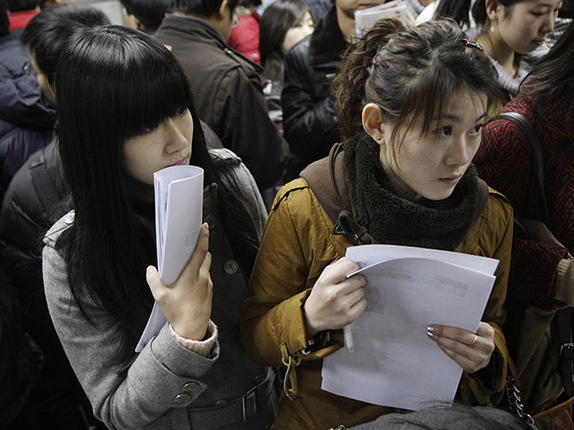 Two job seekers wait to apply for vacancies at a job fair for college graduates in Beijing, China, Tuesday, Feb. 17, 2009. The once ravenous international appetite for Chinese-made goods is shrinking, leading to increased unemployment in the country. Though official unemployment figures often understate the reality, the government has …