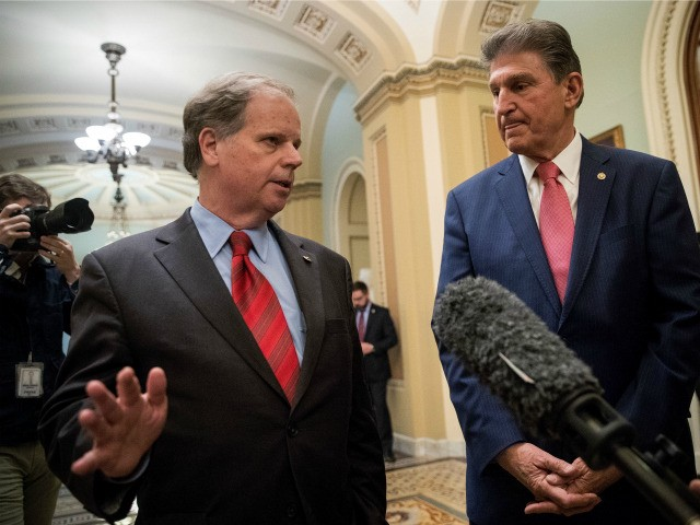 L to R) Sen. Doug Jones (D-AL) and Sen. Joe Manchin (D-WV) speak to reporters after the Senate passed a continuing resolution to fund the federal government, Capitol Hill, January 22, 2018 in Washington, DC. The U.S. Senate has voted to end the shutdown, and Congress will now need to …