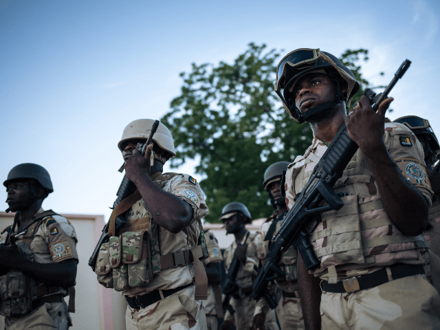 Soldiers conduct the daily flag-lowering ceremony at the Force Multinationale Mixte (FMM) base in Mora, in Cameroon's Far North Region, on September 28, 2018. - Since 2014, the Far North region of Cameroon has witnessed a conflict between the Nigerian Islamic terrorist group Boko Haram and the Cameroonian army. Approximately …