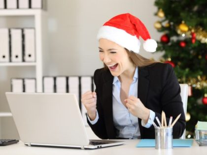 Excited office worker receiving good news on line in a laptop in christmas time