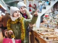 Smiling girl with woman are preparing for a Christmas and choosing a gifts for a their family outdoor. Focus on child