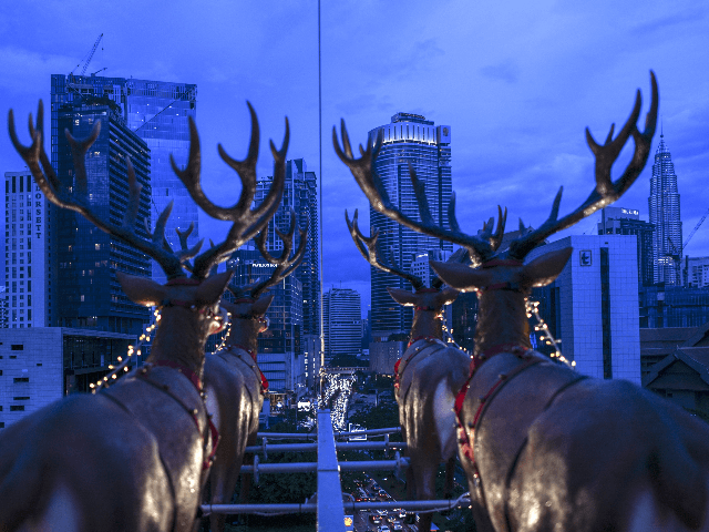 This picture taken on December 5, 2018 shows the iconic Pertonas Twin Towers at right seen from a hanging restaurant suspended by a crane overlooking the skyline of Kuala Lumpur inspired by Santa Claus travelling on a sleigh with reindeers for a Christmas season promotion. - Strapped into rollercoaster-like seats, …