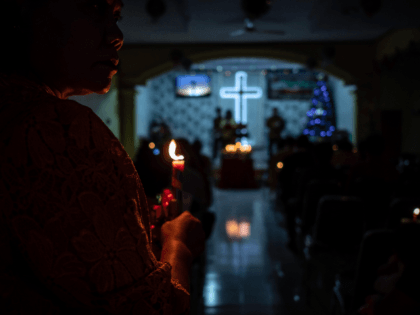 Christians hold candles during Christmas Eve mass at a church in Carita, Banten province, Indonesia.