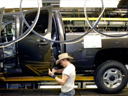 FLINT, MI - JANUARY 24: A person in a cowboy hat works on building a Chevy pickup truck on the assembly line of the General Motors Flint Assembly Plant January 24, 2011 in Flint, Michigan. In response to customer demand GM announced they are adding a third shift and an …