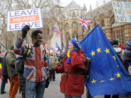"A pro-Brexit activist (L) holding a placard and wearing a union flag-themed shirt talks with an anti-Brexit demonstrator holding an EU flagas they protest near the Houses of Parliament in London on January 29, 2019. - British Prime Minister Theresa May will seek ""legal changes"" to the Brexit deal she …"
