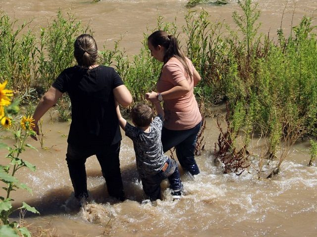 Migrants from Brazil cross the Rio Grande in Ciudad Juarez, State of Chihuahua, Mexico, on June 12, 2019, before turning themselves into US Border Patrol agents to claim asylum. (Photo by HERIKA MARTINEZ / AFP) (Photo credit should read HERIKA MARTINEZ/AFP via Getty Images)