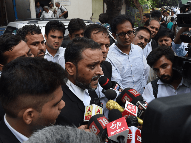 Dharmendra Kumar Mishra (C), lawyer of the rape victim in a high profile case in Uttar Pradesh state, talks to the media outside of a court in New Delhi on August 5, 2019. - A 19-year-old rape victim is fighting for her life in hospital after the car she was …