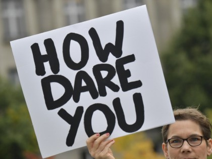 "An environmentalist holds up a poster reading ""How dare you"", quoting Swedish teenage climate activist Greta Thunberg, as she protests outside the German Chancellery where is taking place the weekly cabinet meeting in Berlin on September 25, 2019. (Photo by Tobias SCHWARZ / AFP) (Photo credit should read TOBIAS SCHWARZ/AFP …"