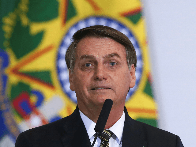 Brazilian President Jair Bolsonaro (C) gestures during a ceremony to commemorate the 300 days of Bolsonaro's administration at Planalto Palace in Brasilia, Brazil, November 5, 2019. (Photo by Sergio LIMA / AFP) (Photo by SERGIO LIMA/AFP via Getty Images)