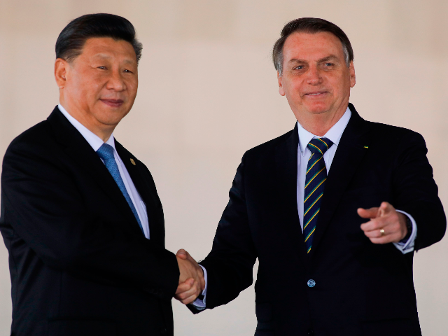China's President Xi Jinping (L) and Brazil's President Jair Bolsonaro (L) shake hands before the 11th BRICS Summit, in Brasilia, on November 14, 2019. - Brazil's President Jair Bolsonaro walked a diplomatic tightrope, as he seeks to boost ties with Beijing and avoid upsetting key ally Donald Trump, on the …