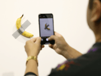 """People post in front of Maurizio Cattelan's """"Comedian"""" presented by Perrotin Gallery and on view at Art Basel Miami 2019 at Miami Beach Convention Center on December 6, 2019 in Miami Beach, Florida. Two of the three editions of the piece, which feature a banana duct-taped to a wall, have …"""