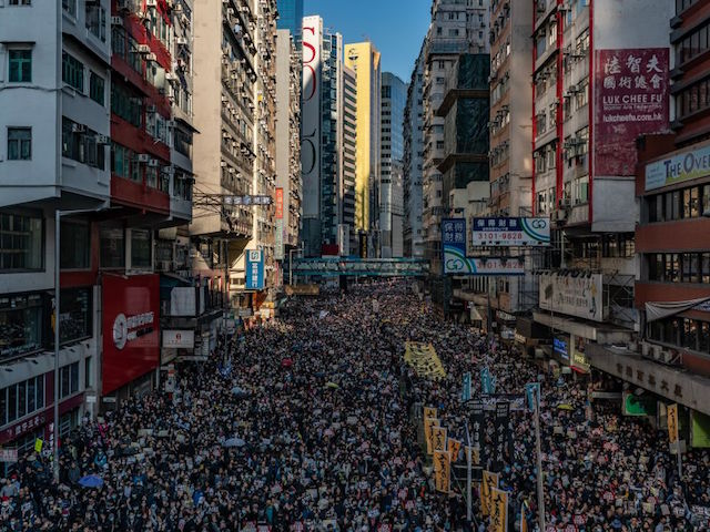 """HONG KONG, CHINA - DECEMBER 8: Pro-democracy protesters march on a street as they take part in a demonstration on December 8, 2019 in Hong Kong, China. Police and firefighters entered the university that has been occupied by pro-democracy protesters for the past 10 days, to remove hazardous items and restore safety. Demonstrations in Hong Kong stretched into its sixth month as pro-democracy groups won the recent District Council elections, continuing demands for an independent inquiry into police brutality, the retraction of the word """"riot"""" to describe the rallies, and genuine universal suffrage. (Photo by Anthony Kwan/Getty Images)"""