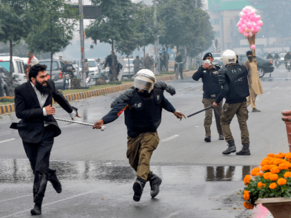 A policeman chases a lawyer (L) following a clash between lawyers and doctors in Lahore on December 11, 2019. - At least three heart patients died on December 11 after a group of lawyers attacked doctors at a cardiac hospital in Pakistan's eastern city of Lahore, officials and ministers said. …