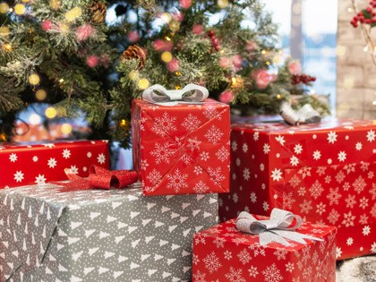 Gift boxes under Christmas tree, New Year home decorations, red wrapping Santa presents, fir tree decorated, beautiful bokeh of garland. Living room with fireplace decorated for Christmas holiday.