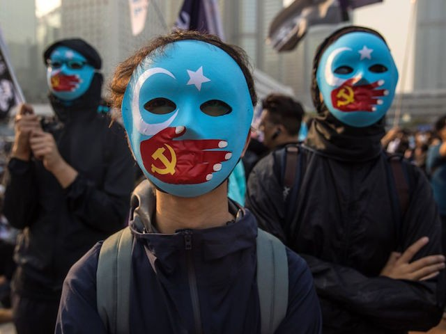 TOPSHOT - Protesters attend a rally in Hong Kong on December 22, 2019 to show support for the Uighur minority in China. - ong Kong riot police broke up a rally in solidarity with China's Uighurs on December 22 as the city's pro-democracy movement likened their plight to that of the oppressed Muslim minority. (Photo by Dale DE LA REY / AFP) (Photo by DALE DE LA REY/AFP via Getty Images)