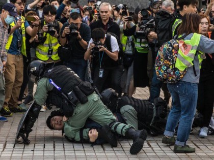 TOPSHOT - Police detain a man during a rally in Hong Kong on December 22, 2019 to show support for the Uighur minority in China. - Hong Kong riot police broke up a solidarity rally for China's Uighurs on December 22 -- with one officer drawing a pistol -- as …