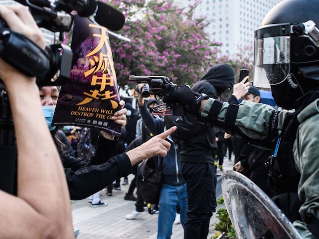 TOPSHOT - A police officer points a pistol during a rally in Hong Kong on December 22, 2019 to show support for the Uighur minority in China. - Hong Kong riot police broke up a solidarity rally for China's Uighurs on December 22 -- with one officer drawing a pistol -- as the city's pro-democracy movement likened their plight to that of the oppressed Muslim minority. (Photo by Anthony WALLACE / AFP) (Photo by ANTHONY WALLACE/AFP via Getty Images)
