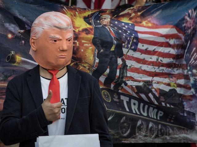 "HONG KONG - DECEMBER 01: A pro-democracy protester wears a face mask of U.S President Donald Trump during a March of Gratitude rally to say thank you to the United States for their support on December 01, 2019 in Hong Kong, China. Demonstrations in Hong Kong stretched into its sixth month as pro-democracy groups won the recent District Council elections, continuing demands for an independent inquiry into police brutality, the retraction of the word ""riot"" to describe the rallies, and genuine universal suffrage. (Photo by Chris McGrath/Getty Images)"