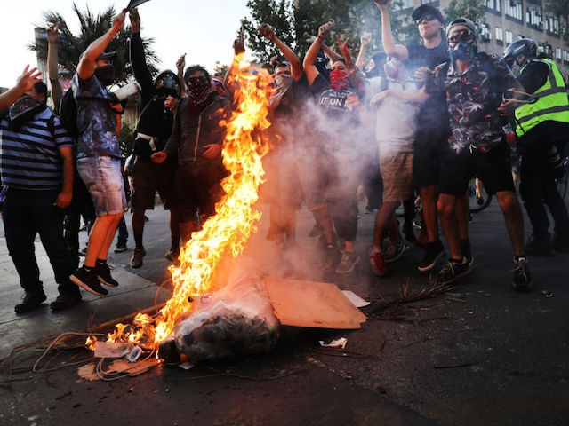 SANTIAGO, CHILE - DECEMBER 05: Protesters burn a barricade in downtown Santiago as demonstrations continue against Chilean President Sebastian Pi√±era on December 05, 2019 in Santiago, Chile. Central Bank of Chile forecasts a 1% growth in GDP for 2019, which will be the worst year for Chilean economy since the …