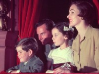 A family watching a Christmas show from a theatre box. (Photo by Housewife/Getty Images)