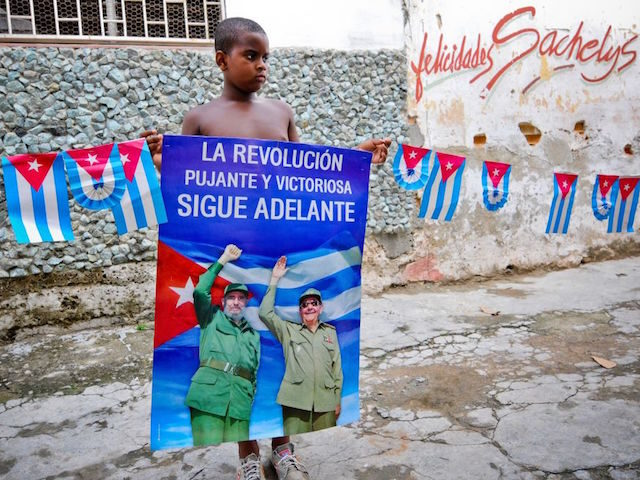A Cuban boy holds a poster of Cuban president Raul Castro and Cuban former president Fidel Castro, on August 12, 2014 in Havana. Fidel Castro will be 88 on Wednesday. AFP PHOTO/YAMIL LAGE (Photo credit should read YAMIL LAGE/AFP via Getty Images)