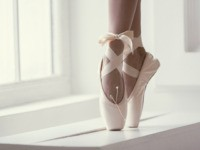 Legs of a ballerina in pink pointe shoes with a bow are dancing near the window