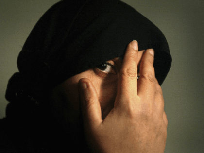 n Iraqi veiled woman covers her face with her hand, March 9, 2005 in Baghdad, Iraq. As violence and religious extremism flourishes in the Iraqi society more women find themselves under pressure to put on the Hijab headscarf. (Photo by Ghaith Abdul-Ahad/Getty Images)