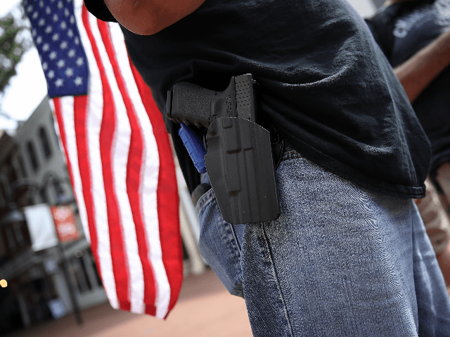 A protester wearing a pistol on his hip stands near the location where a car plowed into a crowd of protestors marching through a downtown shopping district August 12, 2017 in Charlottesville, Virginia. The car allegedly plowed through a crowd, and at least one person has died from the incident, …