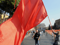 A man waves a red flag during a protest by Italian leftwing opposition parties -- Refoundation Communist, Italian Communists, Greens and Left Democratic -- against the economic policies of the Berlusconi government in Rome on October 11, 2008 AFP PHOTO / ALBERTO PIZZOLI (Photo credit should read ALBERTO PIZZOLI/AFP via …