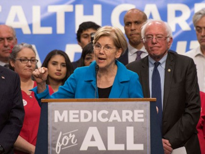 US Senator Elizabeth Warren (C), Democrat from Massachusetts, speaks with US Senator Bernie Sanders (2nd R), Independent from Vermont, as they discusses Medicare for All legislation on Capitol Hill in Washington, DC, on September 13, 2017.
