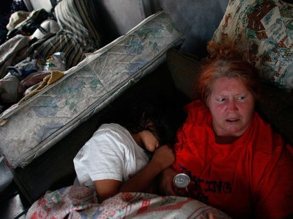 """MIAMI - FEBRUARY 24: Mary Trody and her daughter, Annie Thomas, sit together in a van they parked in front of their foreclosed home that she and her family reoccupied after busting the locks and moving in with the help of the activist group """"Take Back the Land"""" February 24, …"""