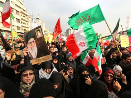 "TOPSHOT - Iranian pro-government demonstrators raise national flags and pictures of the Islamic republic's supreme leader, Ayatollah Ali Khamenei, as they gather in the capital Tehran's central Enghelab Square on November 25, 2019, to condemn days of ""rioting"" that Iran blames on its foreign foes. - In a shock announcement …"