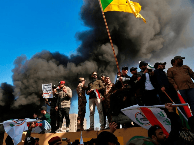 Protesters burn property in front of the U.S. embassy compound, in Baghdad, Iraq, Tuesday, Dec. 31, 2019. Dozens of angry Iraqi Shiite militia supporters broke into the U.S. Embassy compound in Baghdad on Tuesday after smashing a main door and setting fire to a reception area, prompting tear gas and …