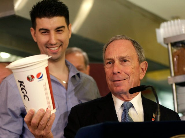 New York City Mayor Michael Bloomberg looks at a 64oz cup, as Lucky's Cafe owner Greg Anagnostopoulos, left, stands behind him, during a news conference at the cafe in New York, Tuesday, March 12, 2013. New Yorkers were still free to gulp from huge sugary drinks Tuesday, after a judge …