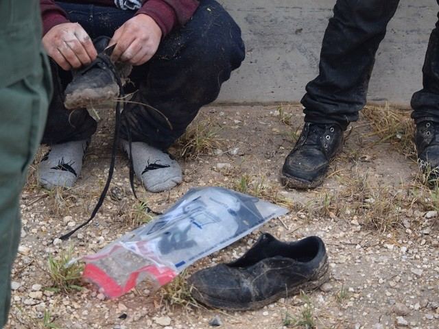 A recently apprehended migrant removes the laces from his shoes before being transported to the Border Patrol station for processing. (Photo: Bob Price/Breitbart Texas)
