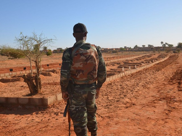 TOPSHOT - A Niger soldier looks at the graves of the soldiers killed before the arrival of the Leaders of the G5 Sahel nations in Niamey, on December 15, 2019. - Leaders of the G5 Sahel nations paid homage at the graves of 71 Niger military personnel killed in a …