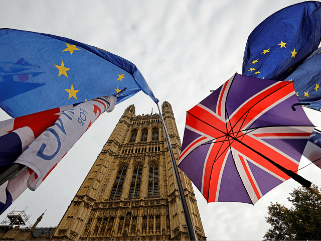 EU flag and Union flag-themed umbrellas of Brexit activists fly outside the Houses of Parliament in London on October 23, 2019. - British Prime Minister Boris Johnson could pivot towards a general election as the EU mulls granting a Brexit deadline extension on Wednesday, after a fresh twist to the …
