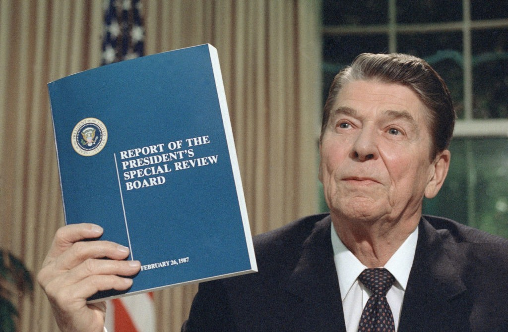 "President Ronald Reagan holds up a copy of the Tower Commission report on the Iran-Contra affair, while posing for photographers after his nationally televised speech from the Oval Office in Washington, Aug. 13, 1987. Reagan said he was ""mad as a hornet"" about damage to his administration from the Iran-Contra affair. (AP Photo/Ron Edmonds)"