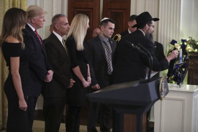 WASHINGTON, DC - DECEMBER 6: (AFP-OUT) Rabbi Avraham Friedman, right, holds the candle to light the menorah next to President Donald Trump, first lady Melania Trump, Andy Pollack (3rd L), Julie Phillips, center, and Hunter Pollack, second right, during a Hanukkah reception in the East Room of the White House …