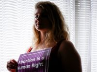 In this Aug. 5, 2019, photo, Beth Vial, who didn't learn she was pregnant until 26 weeks after chronic medical conditions masked her symptoms, poses for a portrait at her home in Portland, Ore. Vial was beyond the point when nearly every abortion clinic in the country would perform the …