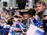 SYDNEY, AUSTRALIA - APRIL 25: Large crowds line George Street and wave Australian flags during the Anzac Day Parade on April 25, 2015 in Sydney, Australia. Australians are celebrating the centenary of the Australian and New Zealand Army Corp (ANZAC) landing on the shores of Gallipoli on April 25, 1915, …
