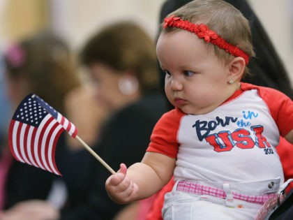 TAMPA, FL - FEBRUARY 14: Cuban immigrant Ed Lacosta holds his baby Melody Grace, 6 months, while sitting with his wife Judy Lacosta at a special Valentine's Day naturalization ceremony for married couples on February 14, 2013 in Tampa, Florida. The U.S. Citizenship and Immigration Service (USCIS) held the Valentine's …