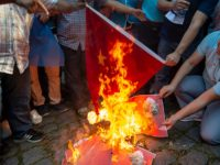Supporters of China's Muslim Uighur minority and Turkish nationalists burn a Chinese flag and a portrait of China's President Xi Jinping, during an anti-China protest in front of the Chinese consulate in Istanbul on October 1, 2019, on the 70th anniversary of the founding of The People's Republic of China. …