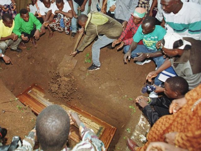 CONAKRY, GUINEA: People surround a grave as the casket of one of the two young Guineans found frozen to death in the undercarriage well of a Belgian Airbus last Monday, is buried, 08 August 1999 in the Cameroon districk cemetery of Conakry. The bodies of Yaguine Koita, 14, and Fode …