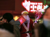 This photo taken on December 24, 2019 shows a vendor dressed as Santa Claus selling toys on a street in Shenyang in China's northeastern Liaoning province. (Photo by STR / AFP) / China OUT (Photo by STR/AFP via Getty Images)