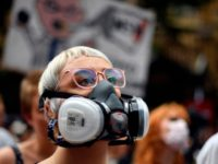 A demonstrator with a gas mask attends a climate protest rally in Sydney on December 11, 2019. - Up to 20,000 protesters rallied in Sydney on December 11 demanding urgent climate action from Australia's government, as bushfire smoke choking the city caused health problems to spike. (Photo by Saeed KHAN …
