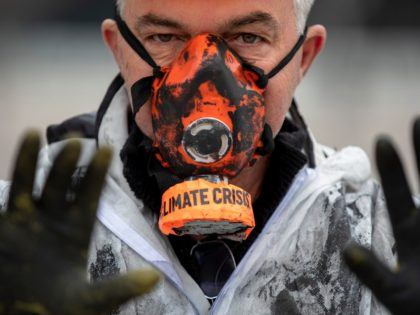 MADRID, SPAIN - DECEMBER 08: A demonstrator wears a mask reading 'Climate Crisis' during a protest outside REPSOL Headquarters on December 08, 2019 in Madrid, Spain. Indigenous leaders and activists are protesting in Madrid against oil contamination and the fossil fuel industry in Brazil because of the damage it provokes …