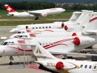 A passenger plane of Swiss International Air Lines takes off behind Dassault's Falcon business jets displayed during the press day of the 8th Annual European Business Aviation Convention & Exhibition (EBACE) on May 19, 2008 in Geneva's International Airport. The annual meeting place for the European business aviation community showcases …