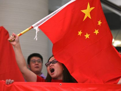 A woman sings and waves the national flag of China during a pro-Beijing flash mob at the Pacific Place shopping mall in Hong Kong on September 24, 2019. - Pro-democracy supporters have taken to Hong Kong's streets for almost four months in the biggest challenge to China's rule since the …